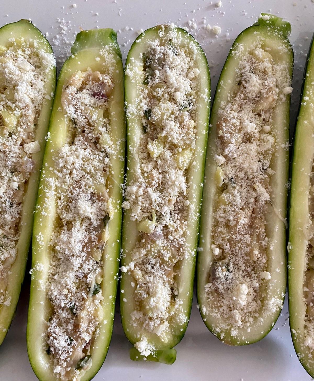 Zucchini boats stuffed with zucchini mixture and sprinkled with Parmesan cheese. #zucchini #howtocookzuchini #howtogrillzucchini #zucchinionthegrill #stuffedzucchini