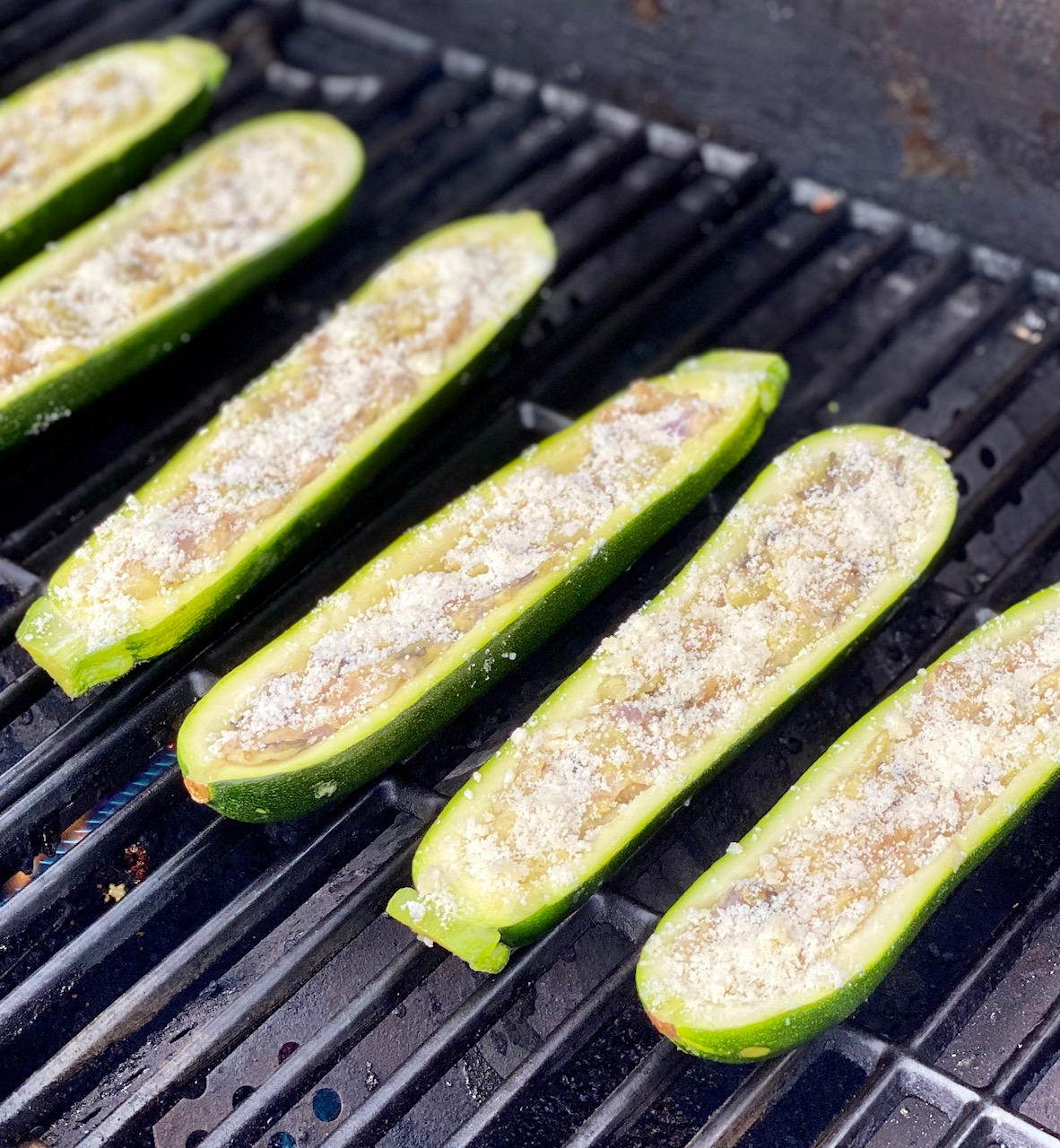 Zucchini boats placed on a grill rack over medium heat. #zucchini #grilledzucchini #grilledvegetables #grilledsidedish #summersidedish #summercookout #grillideas #grillrecipes