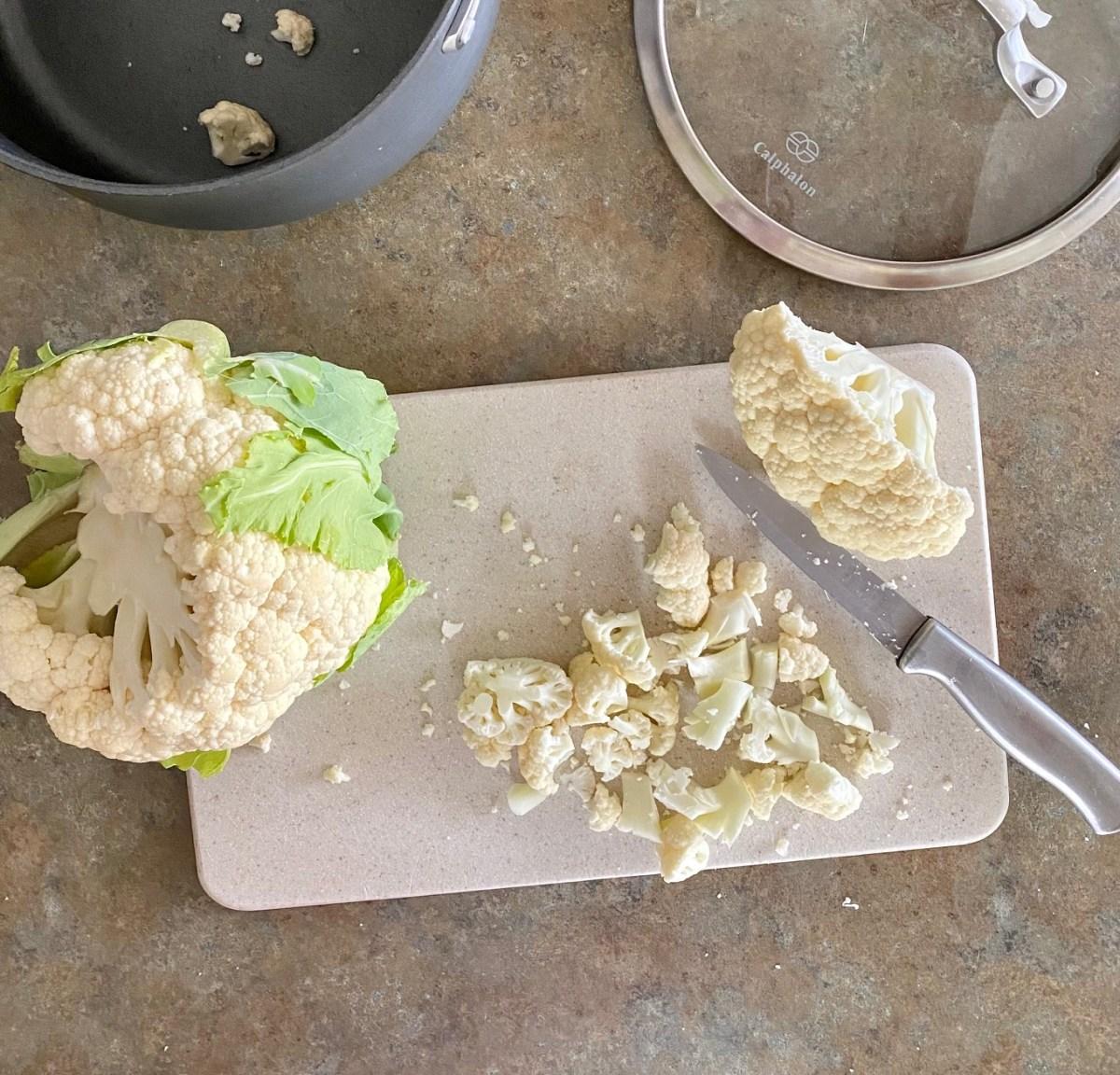 1-inch pieces of cauliflower sliced on a cutting board. #asiagocauliflower #mashedcauliflower #bestmashedcauliflower #howtomakemashedcauliflower #easyketosidedish #easyketorecipes