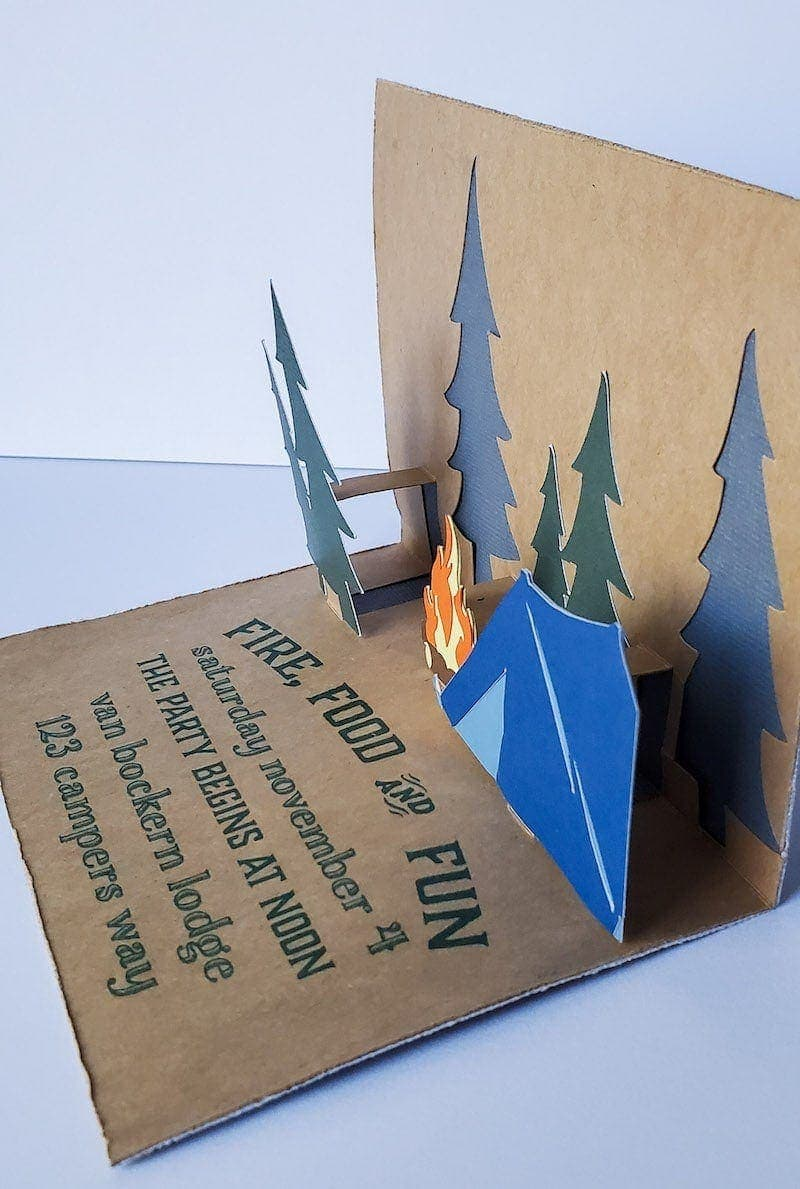 """Side image of invitation. Brown craft paper with deep green pop up trees, orange and yellow campfire, and blue tent. Text in dark green reads """"Fire, Food & Fun; saturday november 4; THE PARTY BEGINS AT NOON; van bockern lodge; 123 campers way"""""""