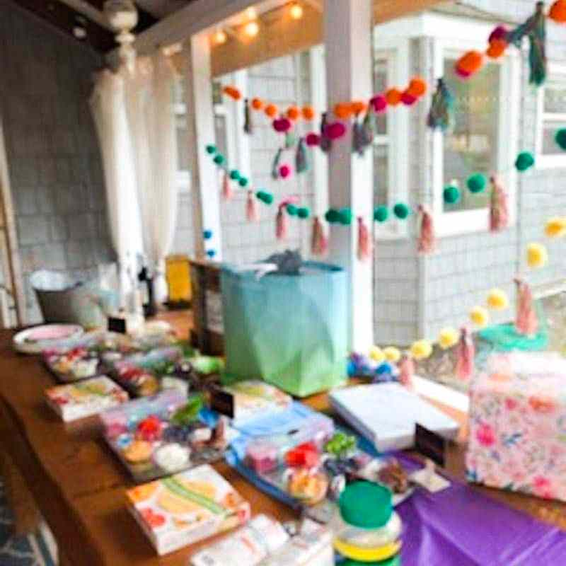 Photo of food table, pom pom and tassels hanging on wall, presents on the table