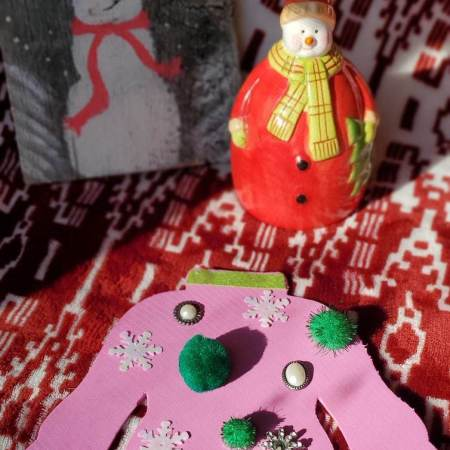 Photo of pink sweater made from foam with green pom poms, snowflake sequins and jewels. Snowmen in background