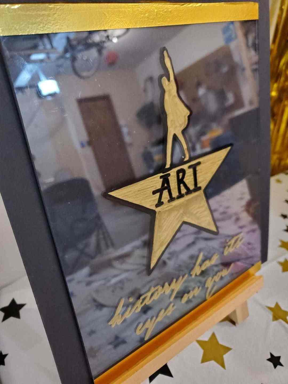 Acrylic sign with Hamilton logo that says ARI, history has its eyes on you