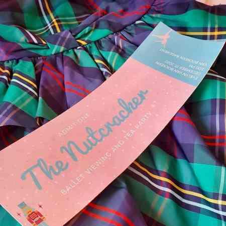 Photo of Nutcracker invitation laying on a plaid dress