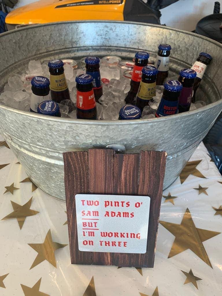Bucket of beer with a wood sign: TWO PINTS O' SAM ADAMS BUT I'M WORKING ON THREE