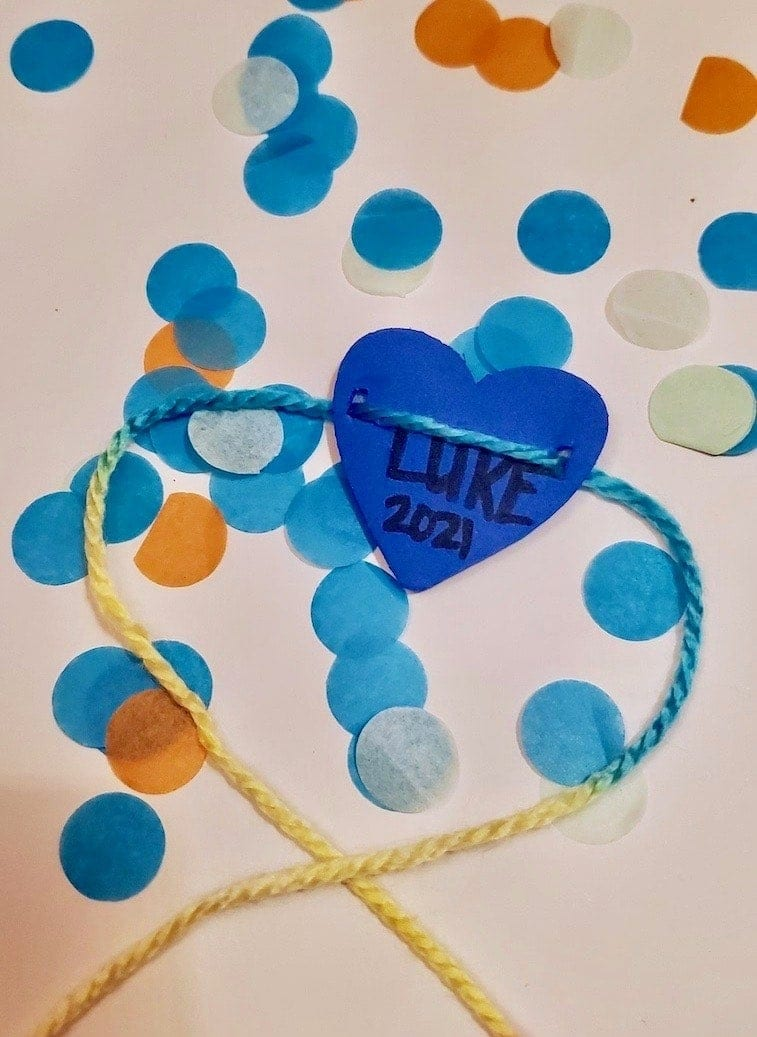 Photo of the back of a blue heart bracelet with written text: LUKE 2021