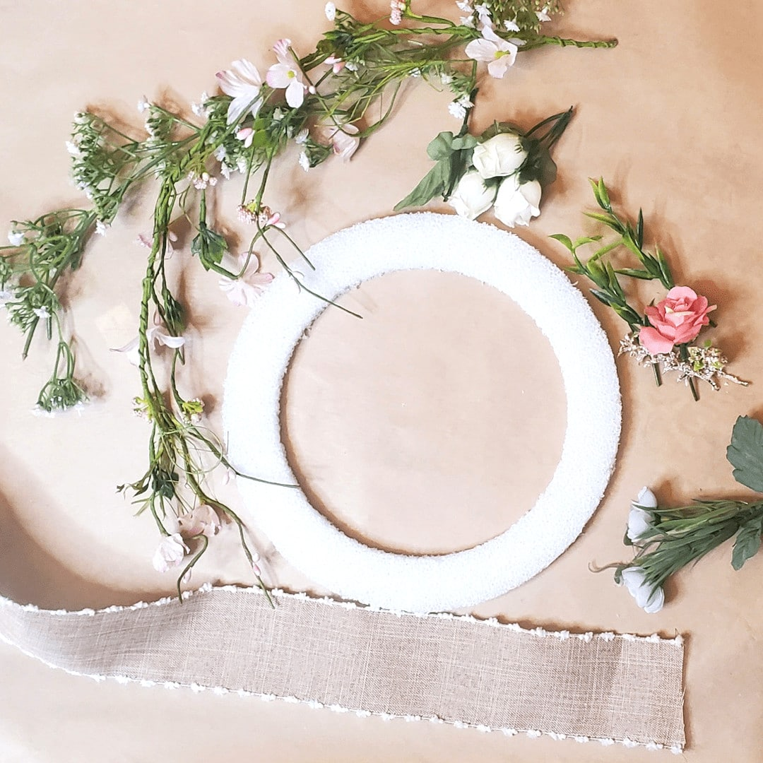 picture of foam wreath form, floral and greanery, and ribbon