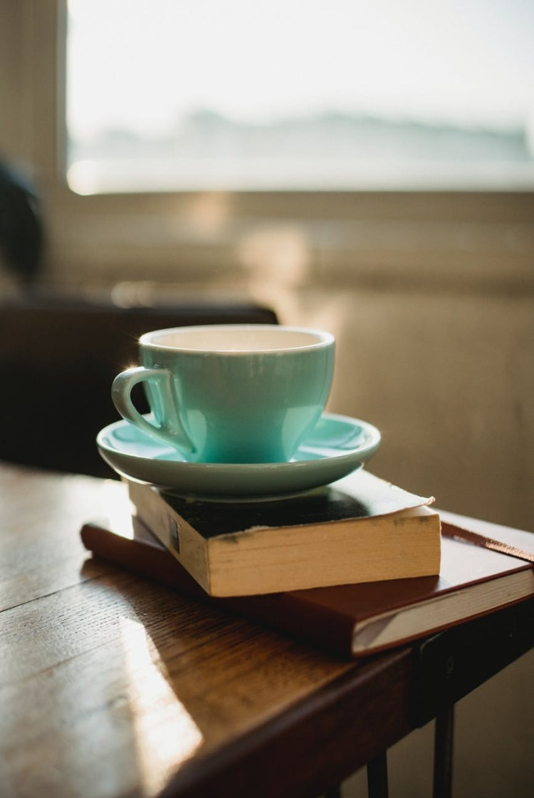 cup of hot beverage on books