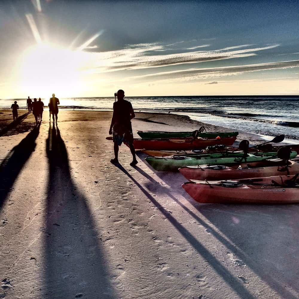 Sunset family tour with kayaks on beach