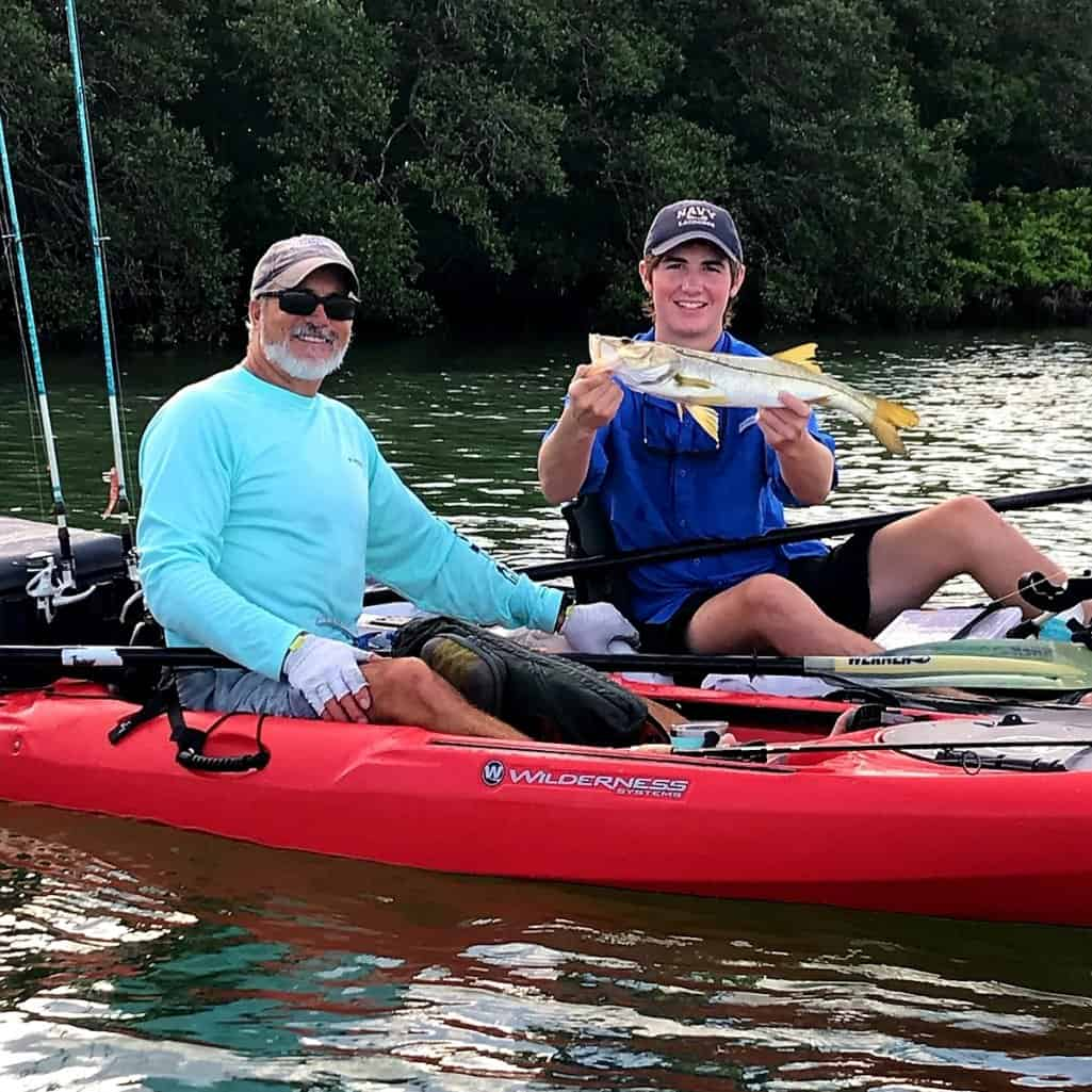 Fishing guide and angler sitting in kayaks holding their catch common snook in Longboat Key, Florida
