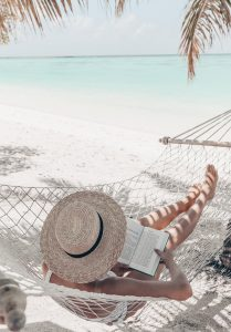woman relaxing and reading while sitting in hammock on beach