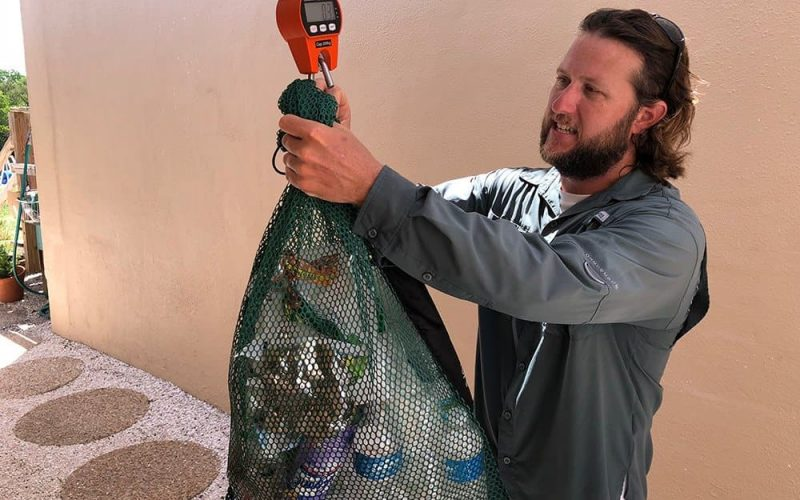Happy Paddler weighing litter collected during the Paddle Clean Initiative