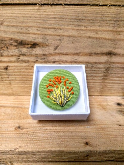 green stitched brooch