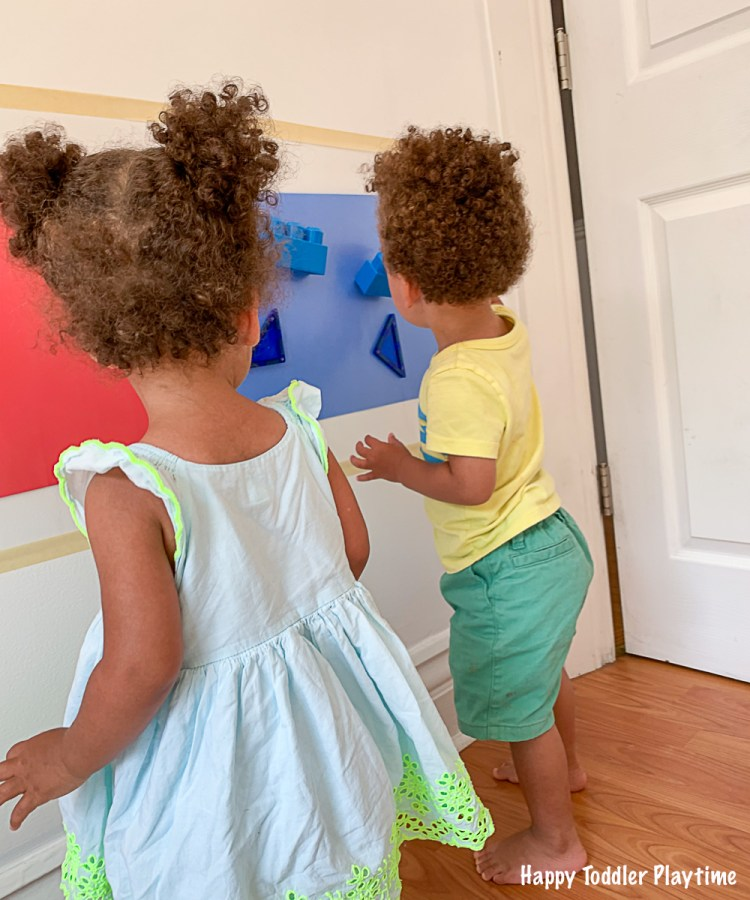Twin toddlers Colour sorting red and  blue on a sticky wall
