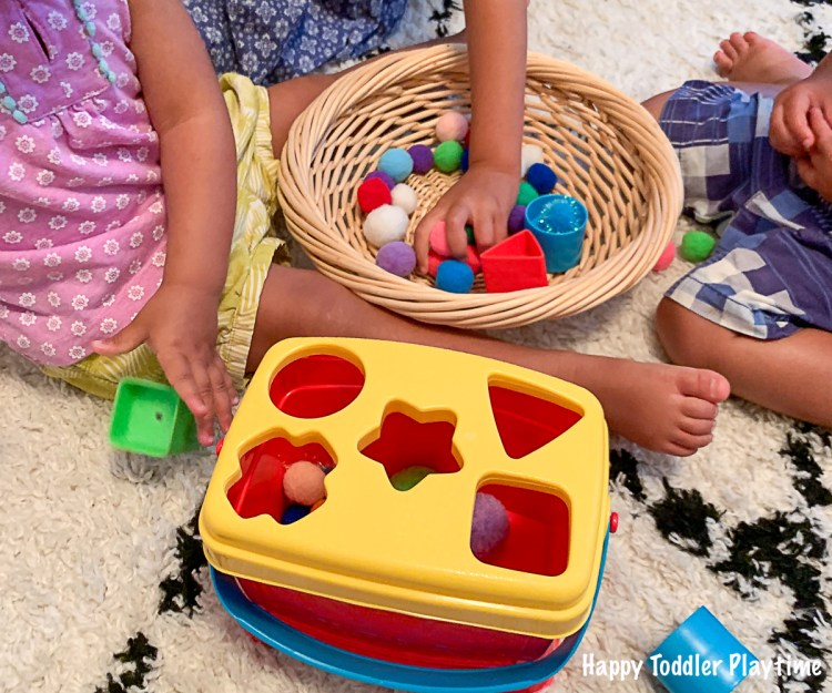 a Pom Pom sorting activity using a shape sorter