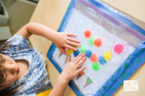 Moving the pompoms in the sensory bag