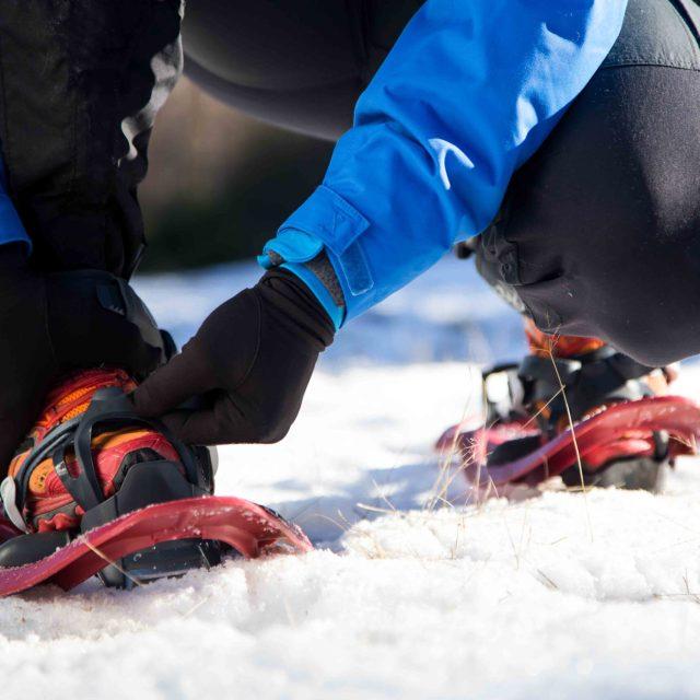 Portrait d'un jeune homme se préparant à marcher en raquettes sur fond d'hiver.