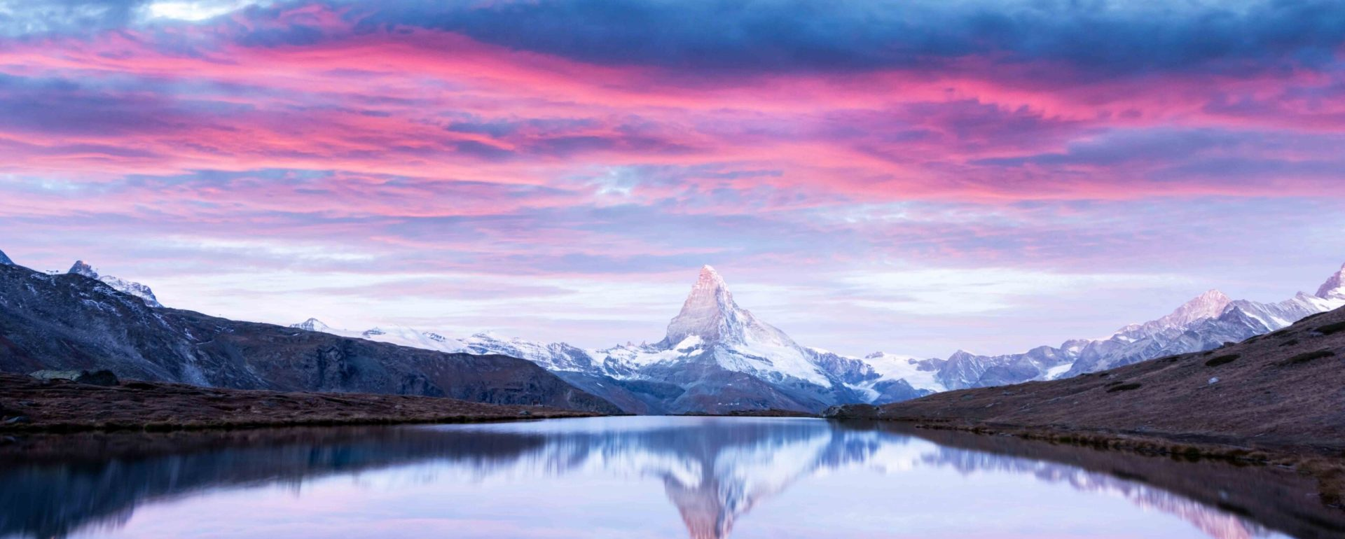 Magic landscape with colorful sunrise on Stellisee lake. Snowy Matterhorn Cervino peak with reflection in clear water. Zermatt, Swiss Alps
