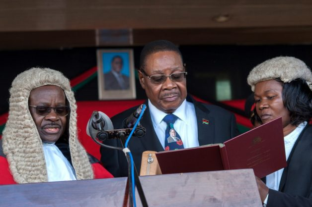 (FILES) In this file photo taken on May 28, 2019 Malawi's President elect Arthur Peter Mutharika is sworn in for his second term by Chief Justice Andrew Nyirenda (L) and Registrar of the high Court and Supreme court of appeal Agnes Patemba (R) at Kamuzu Stadium in Blantyre after a contentious election marred by allegations of fraud and vote-rigging. - Malawi's constitutional court on February 3, 2020 has cancelled presidential vote result. (Photo by AMOS GUMULIRA / AFP)