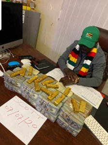 Sakupwanya poses with piles upon piles of bricks of cash in US dollars as well as gold barS