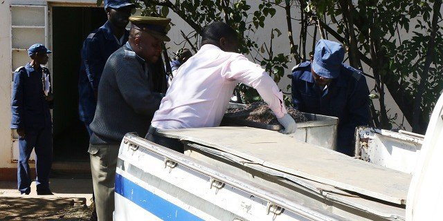 Police carrying coffin of murder victim