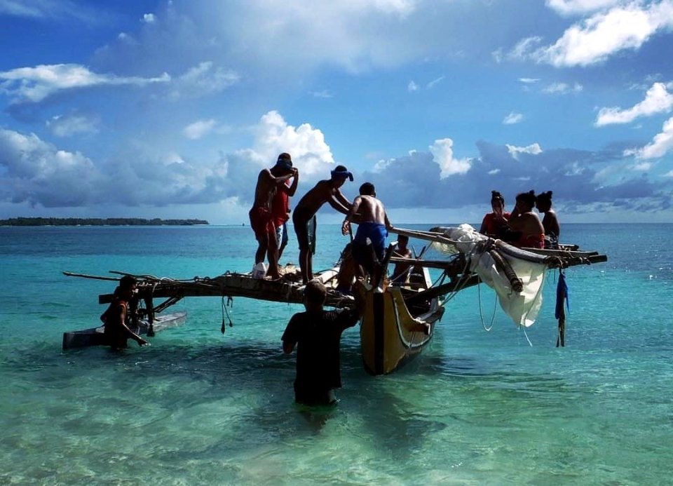 An indigenous sailboat with several tanned working people on it – the art of sailing