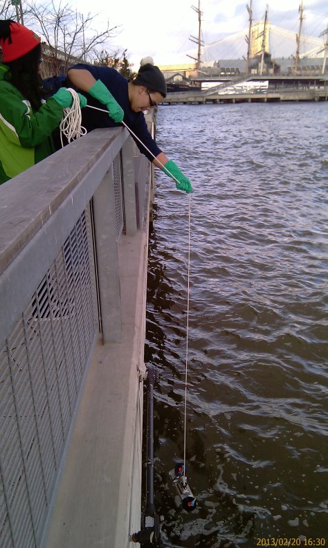 Tahirah and Orlando pull up their group's water sample from the East River