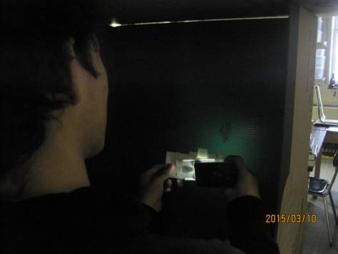 Jose Projecting an Amoeba on to a dark wall.