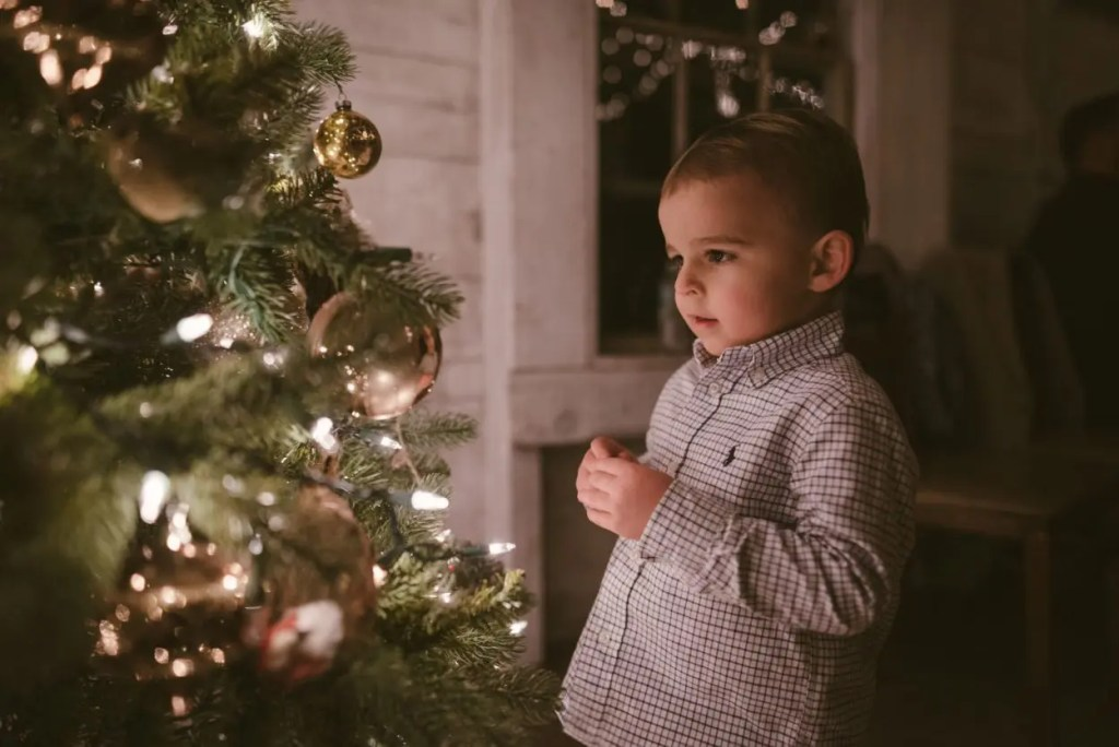 child looks at christmas tree