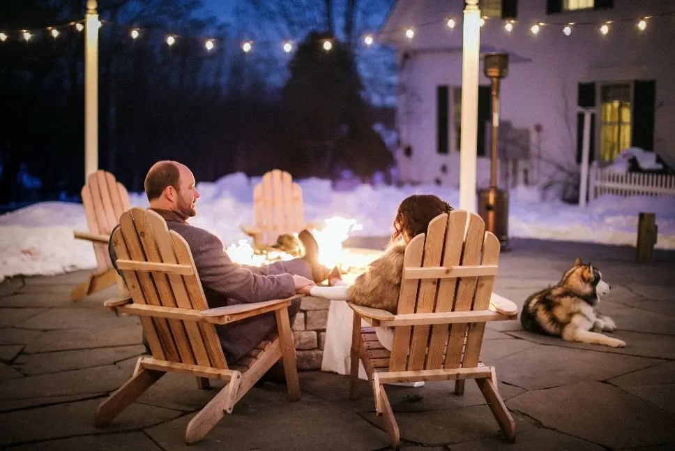 Winter wedding relaxes by the firepit with their dog at Hardy Farm