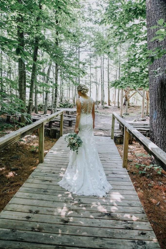 Bride walking into woodland chapel