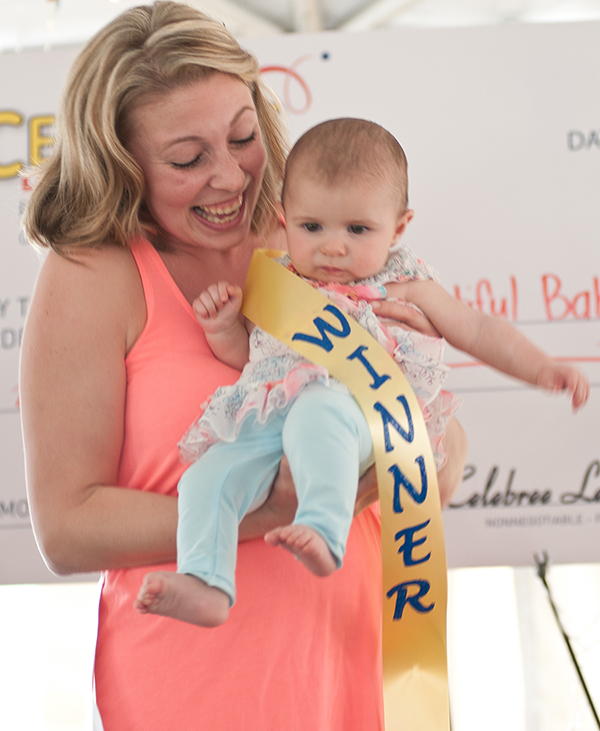 Held by her mother Heather Vogt, six month-old Charlotte Vogt accepts her title of grand prize winner in the 2015 Harford's Most Beautiful Baby Contest (Infant).