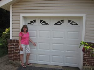 Sheila Mulligan poses with her new garage door, professionally installed by Carl's Door Service in less than two hours.