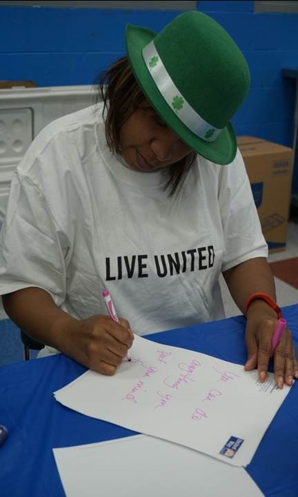 Dominque Mattocks, Dept. of Community Services, writing encouraging messages to the children for their bagged lunches