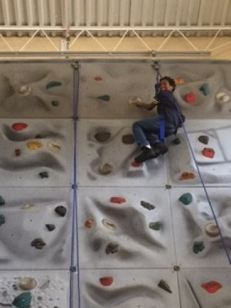 Amar Mack reaches the top of the rock wall during our field trip to the Ward Y Center