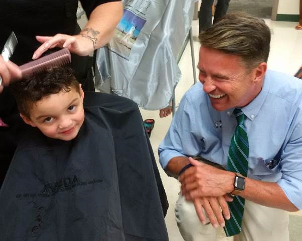 Four-year-old Jordan Schulze getting a haircut for pre-school with encouragement from Harford County Executive Barry Glassman