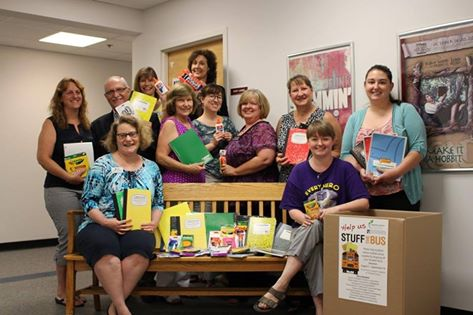 "Staff of the Harford County Public Library (HCPL) pose by a collection bin for the GEEF ""Stuff the Bus"" collection for school supplies. Items are being collected at all HCPL branches and will be distributed to financially disadvantaged students in Harford County."