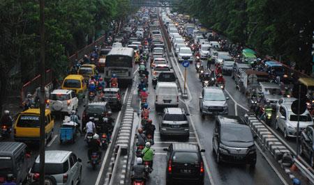 Kerusakan lampu TL di beberapa ruas jalan ditambah guyuran hujan deras memacetkan Surabaya, Rabu (30/11). [trie diana]