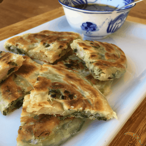 scallion pancakes on a white square plate served with spicy soy sauce