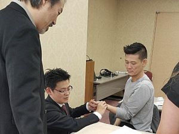 Japanese Acupuncture study-abroad tourにて参加者の脈を診る足立繁久の写真