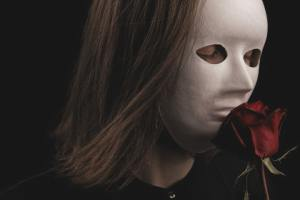 Young woman in white face mask, covers whole face, smelling a deep maroon rose. Dark in nature