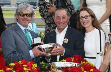Claus Andersen   Two-time Hambletonian champion Blair Burgess (left) was on hand to present the winning trainer trophy to fellow Canadian Rick Zeron (with wife Joyce Zeron).
