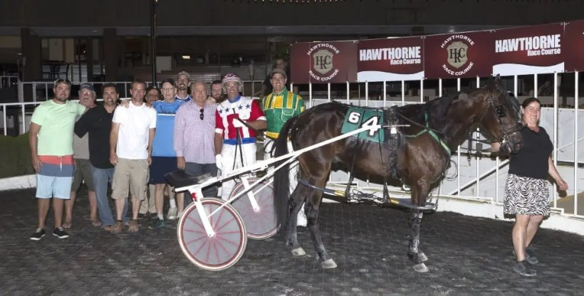 courtesy Hawthorne Race Course | Vegas Bomb in the winner's circle on June 28 with Banks (green and yellow colors) and driver Casey Leonard and connections.