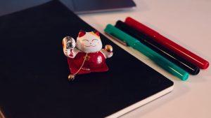Un Maneki-neko accompagné de stylos de couleurs sur un carnet noir