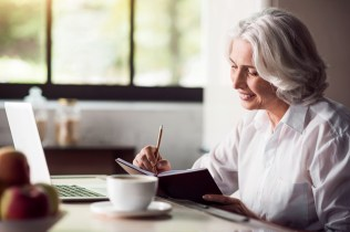 Grey-haired lady taking notes with pencil and using laptop