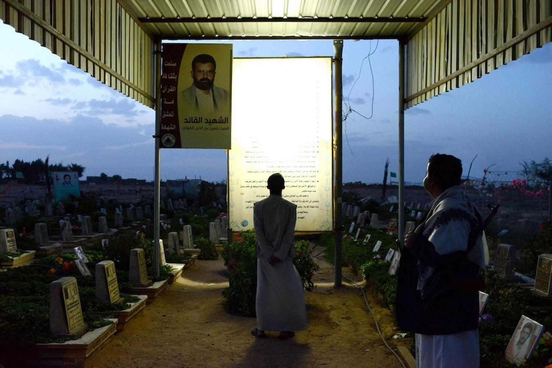 Two Yemeni men visit a graveyard and memorial of war martyrs.