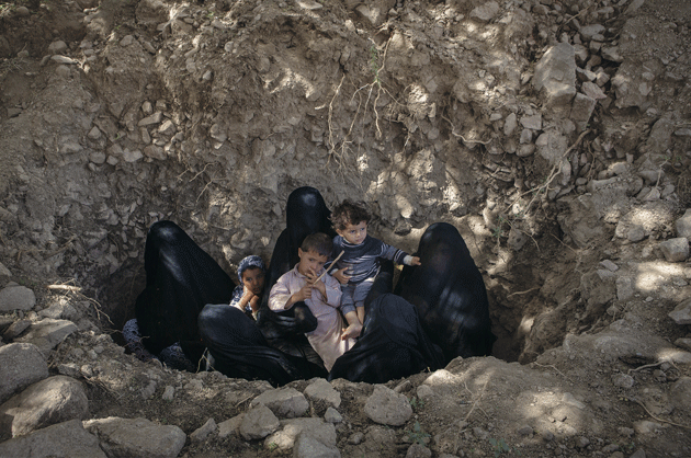 Women and children who were displaced from their village by air strikes seek shelter in the ground near Fella, in Saada governorate, where a local school housed them. When the women hear warplanes or antiaircraft fire, they feel safer in the ground. Photograph by Maria Turchenkova