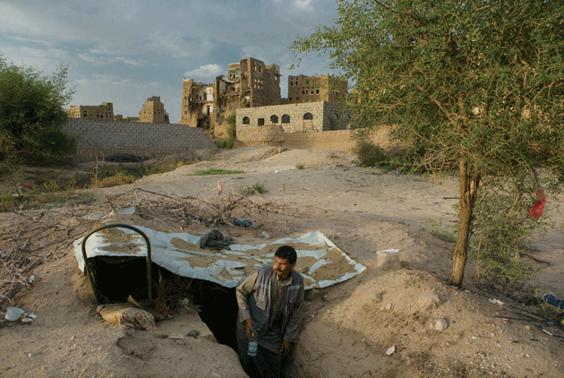 A man stands in a shelter dug into the ground in Rahban, on the outskirts of Saada city. Much of Rahban was destroyed by a series of air strikes in March 2015. Photograph by Maria Turchenkova