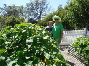 Lynn and Suzanne enjoying Pat's gigantic cucumber plant.