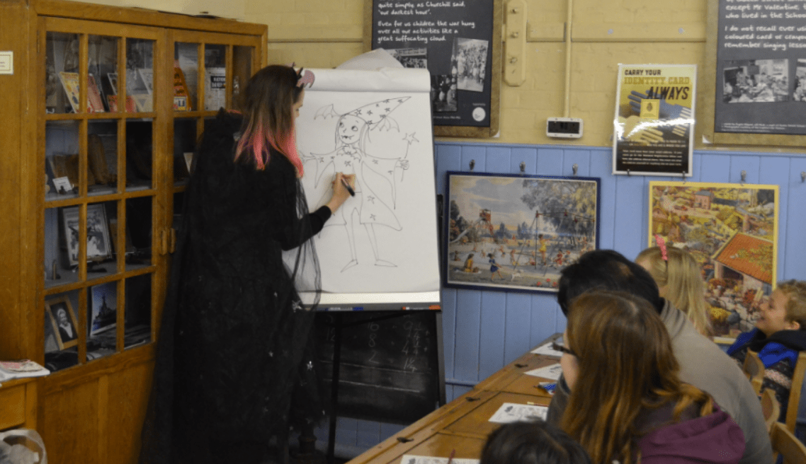 Harriet Muncaster drawing an audience member as a Vampire Wizard at Hitchin Childrens Book Festival